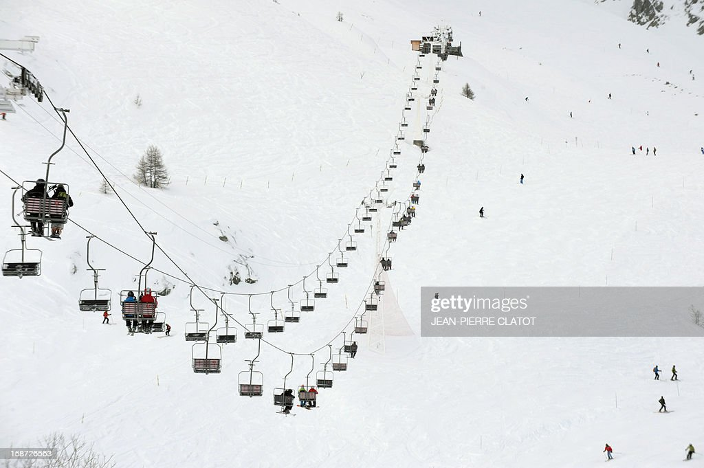 Skiers ride a chair-lift at the Grands Monets slopes part of the Mont-Blanc mountain chain on December 26, 2012 in the Chamonix valley, French Alps. AFP PHOTO / Jean Pierre Clatot