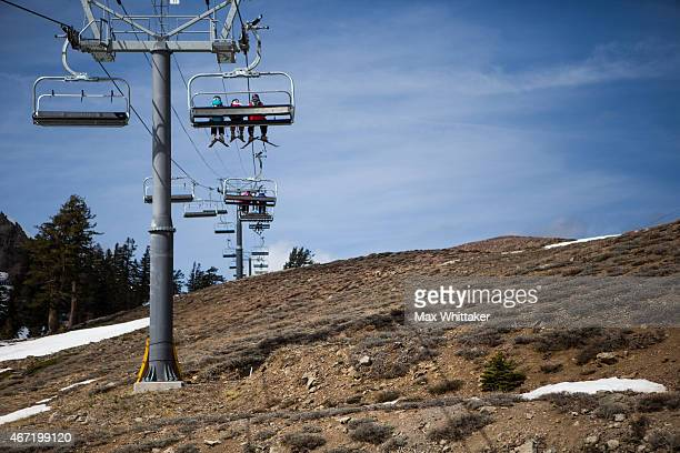 Skiers ride a chairlift over dry ground at Squaw Valley Ski Resort March 21 2015 in Olympic Valley California Many Tahoearea ski resorts have closed...