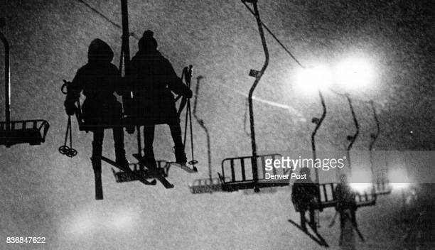 Skiers Silhouetted Against SnowFlecked Glare Ride The Chairlift Credit Denver Post