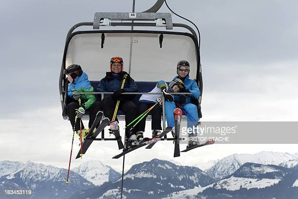 Skier's sit in a ski cable car in front of the mountains at the ski area near the Bavarian village Ofterschwang southern Germany on March10 2013 AFP...