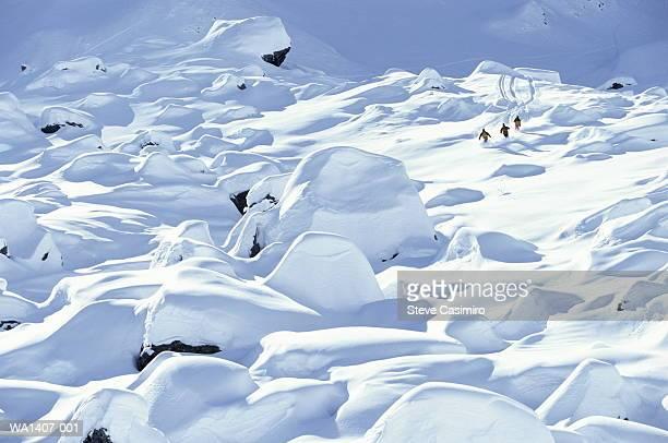 Skiers skiing between moguls