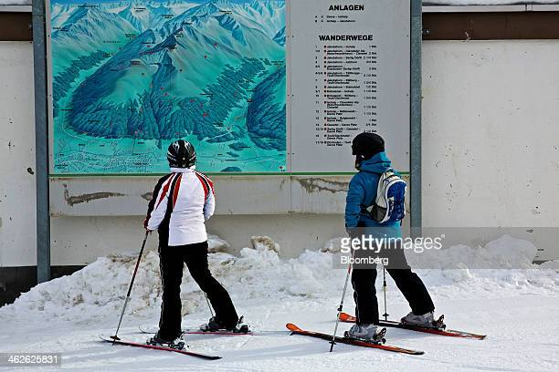 Skiers stand on their skis as they look at a piste map of the Jakobshorn mountain in Davos Switzerland on Monday Jan 13 2014 Next week the business...