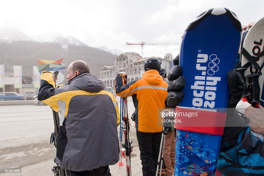 Skiers wait for a transit bus on February 11, 2013 on a busy stretch of road amid signs of the ongoing construction work in Krasnaya Polyana, near Sochi. With a year to go until the Sochi 2014 Winter Games, tests events and World Championship competitions are underway.