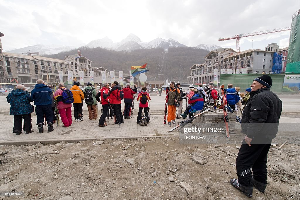 Skiers wait for a transit bus on February 11, 2013 on a busy stretch of road amid signs of the ongoing construction work in Krasnaya Polyana, near Sochi. With a year to go until the Sochi 2014 Winter Games, tests events and World Championship competitions are underway. AFP PHOTO / LEON NEAL