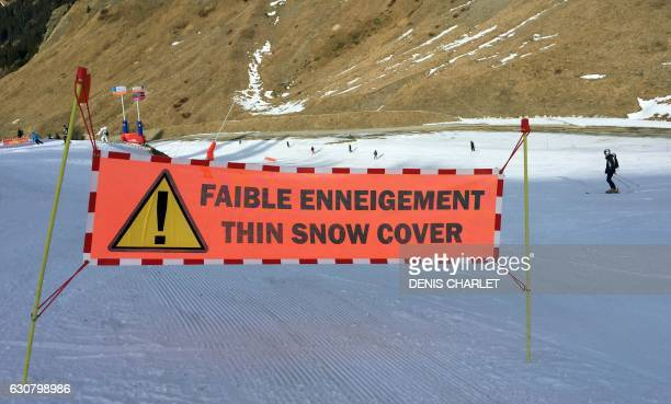 Skiers ski past a sign on a slope on January 1 2017 in the French Alps resort of Flaine / AFP / DENIS CHARLET