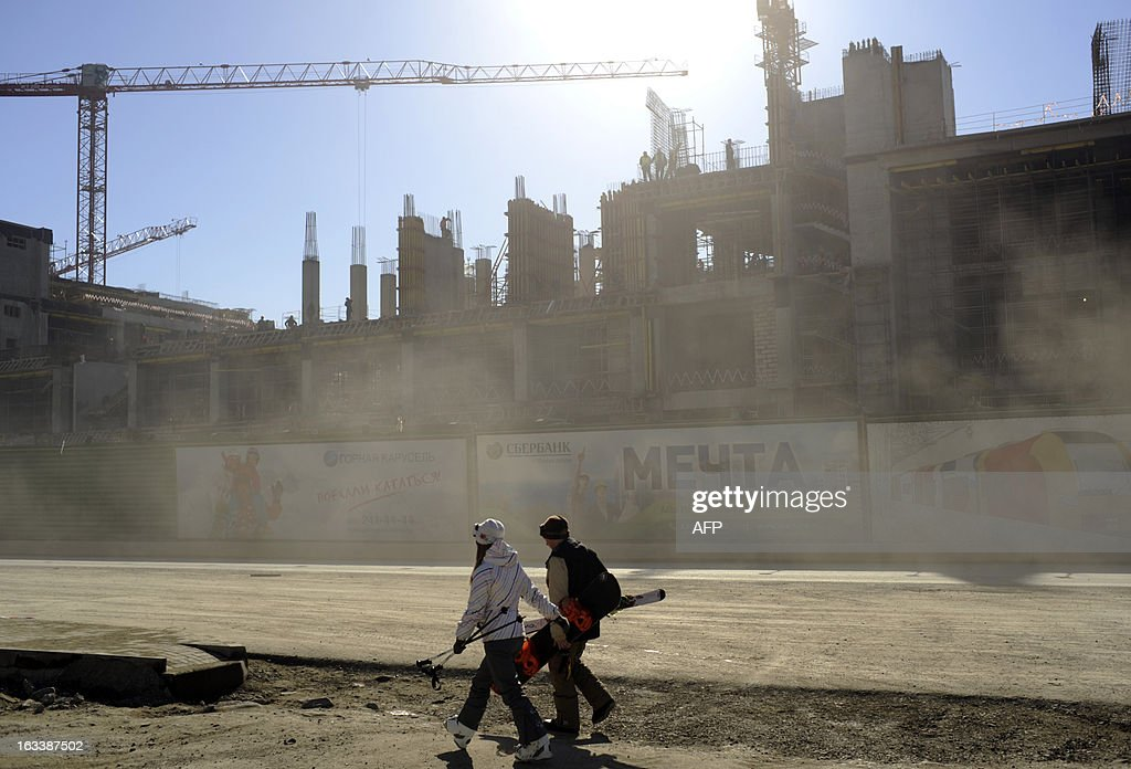 Skiers walk past of the ongoing construction work in Krasnaya Polyana outside the Russian Black Sea resort of Sochi on March 8, 2013. With a year to go until the Sochi 2014 Winter Games, construction work continues as tests events are underway.