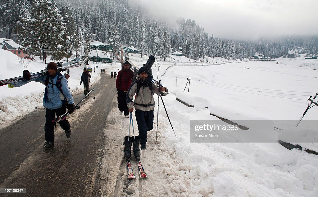 Skiers walk with skis during the season's first snowfall, on November 29, 2012 in Gulmarg, 54 km (35 miles) to the west of Srinagar, the summer capital of Indian-administered Kashmir, India. As the Kashmir valley received heavy snowfall in its upper reaches, the 434-km Srinagar-Leh National highway, the highest motorable road in the world, was closed to traffic. The famous ski resort of Gulmarg also experienced the first heavy snowfall of the season, officials said. Gulmarg, located less than six miles from the ceasefire line or Line of Control (LoC) that divides Kashmir between India and Pakistan, is known for long-run skiing, snow-boarding, heli-skiing and steep mountains.