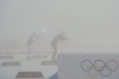 Skiers warm up as fog descends at the Laura CrossCountry Ski and Biathlon Center as the Men's Biathlon 15 km Mass Start has been postponed for the...