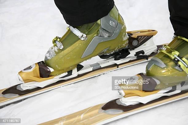 Skiier putting on skis