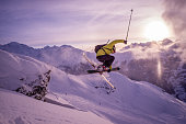 A skiier flies through the air on the ski slopes above Verbier in the Swiss alps. The mountains are blanketed in fresh snow and the sun is setting behind Mont Blanc and the Chamonix range.