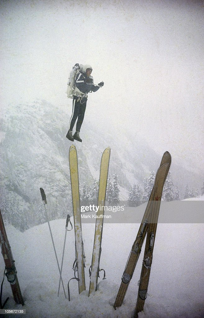 View of skier wearing rocket belt and backpack which enables him to fly up mountains and ski down them. Mount Baker, CA