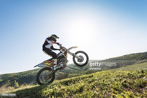 Skilful motocross rider on a back wheel riding uphill.