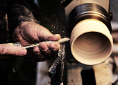hand of an old artisan during the work of the wooden piece with the lathe i