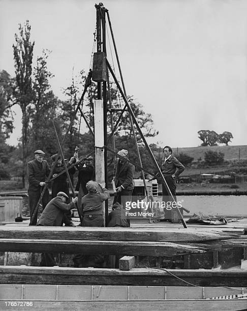 Skilled workmen install one of the 517 piles on the course in preparation for the Henley Royal Regatta HenleyOnThames England 20th May 1950