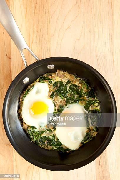 Poële à frire tout juste sorties du four, des œufs et aux épinards