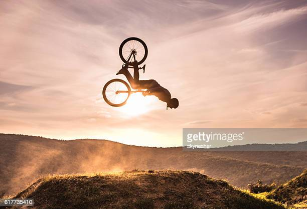 Skillful cyclist doing backflip against the sky at sunset.