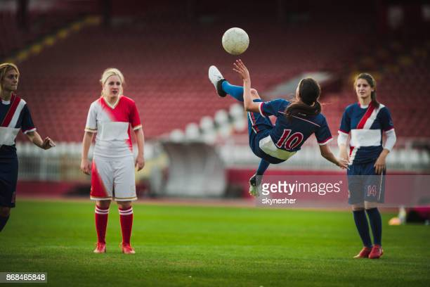 Skillful female soccer striker doing bicycle kick during the game.