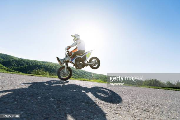 Skillful motorcyclist balancing on front wheel on a road.