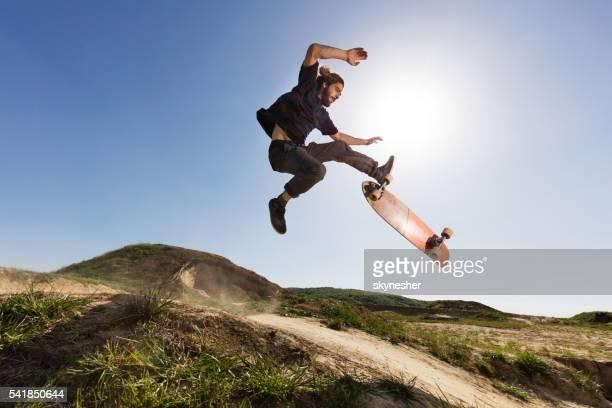 Skillful skateboarder practicing Ollie against the blue sky.