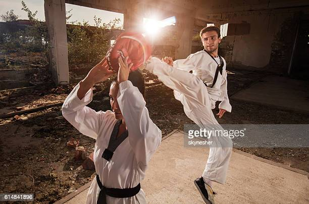 Skillful taekwondo fighter practicing jump kick with sparring partner.