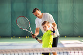 Professional male tennis player is explaining to child how to play tennis. He is adjusting racket in childish hands. Boy is standing and looking forward with seriousness. Portrait