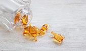 Skin and hair vitamin serum orange capsules on white table