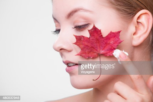 Skin care. Face of young woman girl with maple leaf. : Stock Photo
