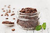 Body scrub of ground coffee, sugar and coconut oil in glass jar on white rustic table, homemade cosmetic for peeling and spa care