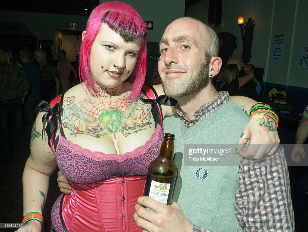 CONTENT] A skinhead scooterist couple pose in a nightclub.They are attending a scooter rally.She is heavily tattooed with pink hair and he is smiling whilst clutching a beer bottle.