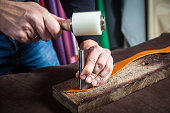 A close-up of a man skinner makes holes  with the help of a special hammer in the brown belt of full-length leather for fasteners on the wrinkled desk in the workshop. Saddler  manufactures a belt