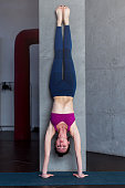 Skinny barefoot woman in sportswear doing handstand against the wall indoors.