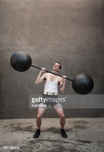Skinny Caucasian weight lifter straining