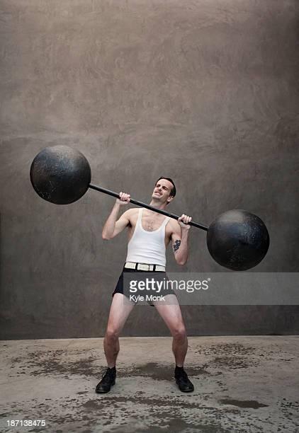 Skinny Caucasian weight lifter straining