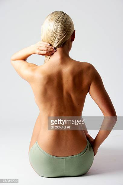 Skinny young woman holding her blonde hair, rear view