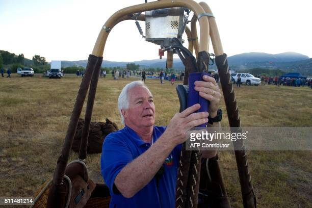 Skip Howes of Colorado Springs Colorado prepares the altimeter and temperature gauge he will use while flying the balloon Wildfire during the 36th...