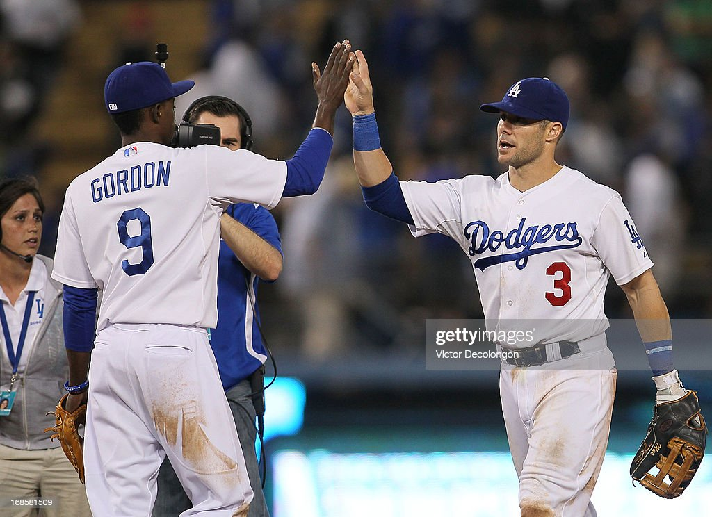 Skip Schumaker #3 and Dee Gordon #9 of the Los Angeles Dodgers celebrate after defeating the Miami Marlins 7-1 in their MLB game at Dodger Stadium on May 11, 2013 in Los Angeles, California.