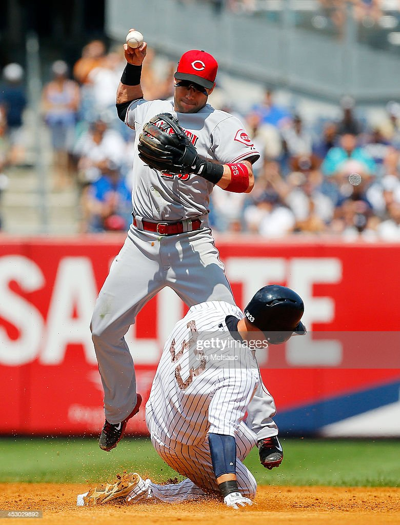 Skip Schumaker of the Cincinnati Reds in action against Kelly Johnson of the New York Yankees at Yankee Stadium on July 20 2014 in the Bronx borough...