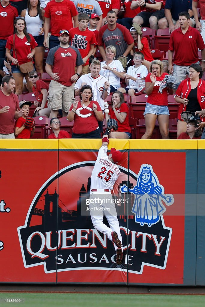 Skip Schumaker of the Cincinnati Reds jumps but is unable to catch the ball hit by Chris Coghlan of the Chicago Cubs for a tworun home run in the...