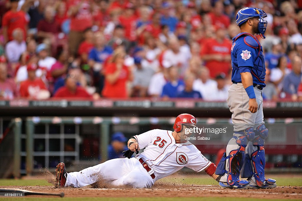Skip Schumaker #25 of the Cincinnati Reds slides home safely for the the Reds' third run of the fifth inning as catcher Welington Castillo #5 of the Chicago Cubs waits for the ball at Great American Ball Park on July 9, 2014 in Cincinnati, Ohio. Cincinnati defeated Chicago 4-1.