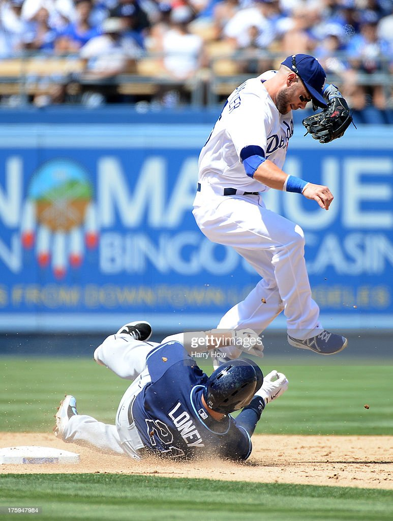 <a gi-track='captionPersonalityLinkClicked' href=/galleries/search?phrase=Skip+Schumaker&family=editorial&specificpeople=640599 ng-click='$event.stopPropagation()'>Skip Schumaker</a> #55 of the Los Angeles Dodgers avoids the slide of <a gi-track='captionPersonalityLinkClicked' href=/galleries/search?phrase=James+Loney&family=editorial&specificpeople=636293 ng-click='$event.stopPropagation()'>James Loney</a> #21 of the Tampa Bay Rays to break up a double play during the fourth inning at Dodger Stadium on August 10, 2013 in Los Angeles, California.