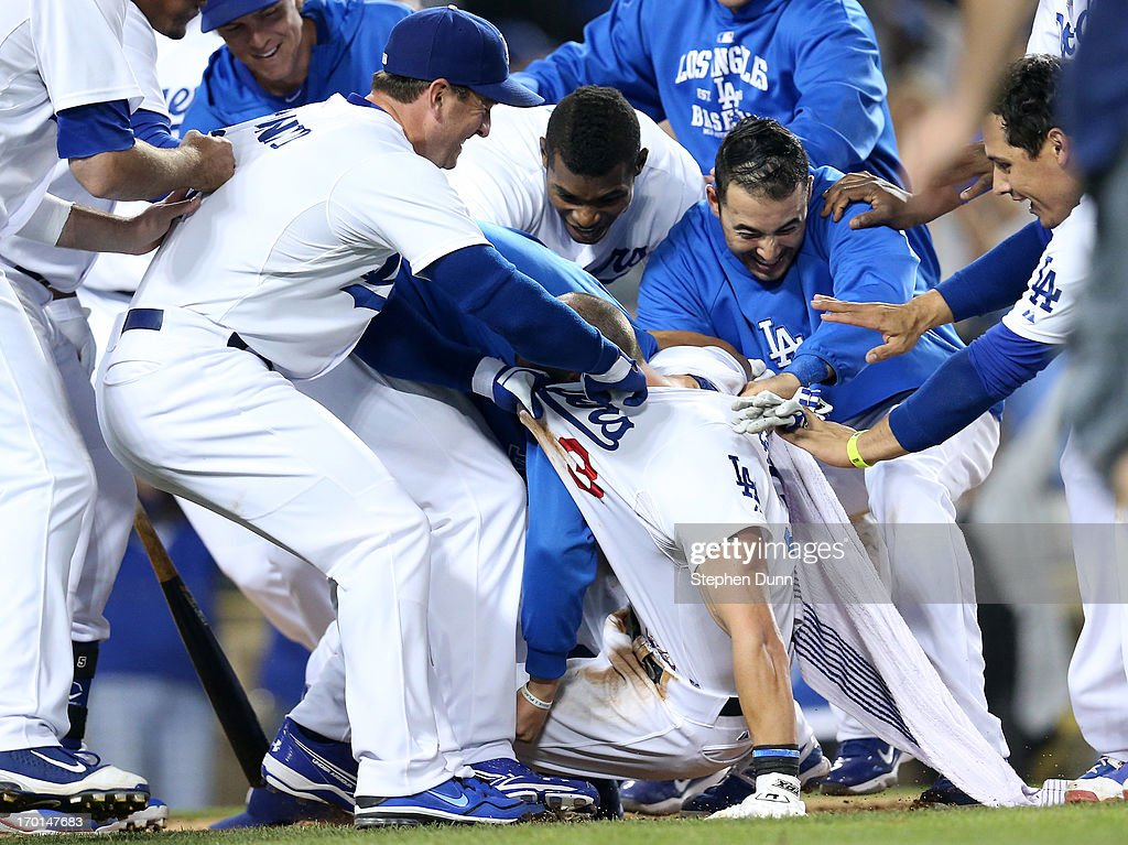 Skip Schumaker #3 of the Los Angeles Dodgers is mobbed and has his jersey torn off by treammates after scoring the winning run on a wild pitch in the 10th inning against the Atlanta Braves at Dodger Stadium on June 7, 2013 in Los Angeles, California. The Dodgers won 2-1 in 10 innings.