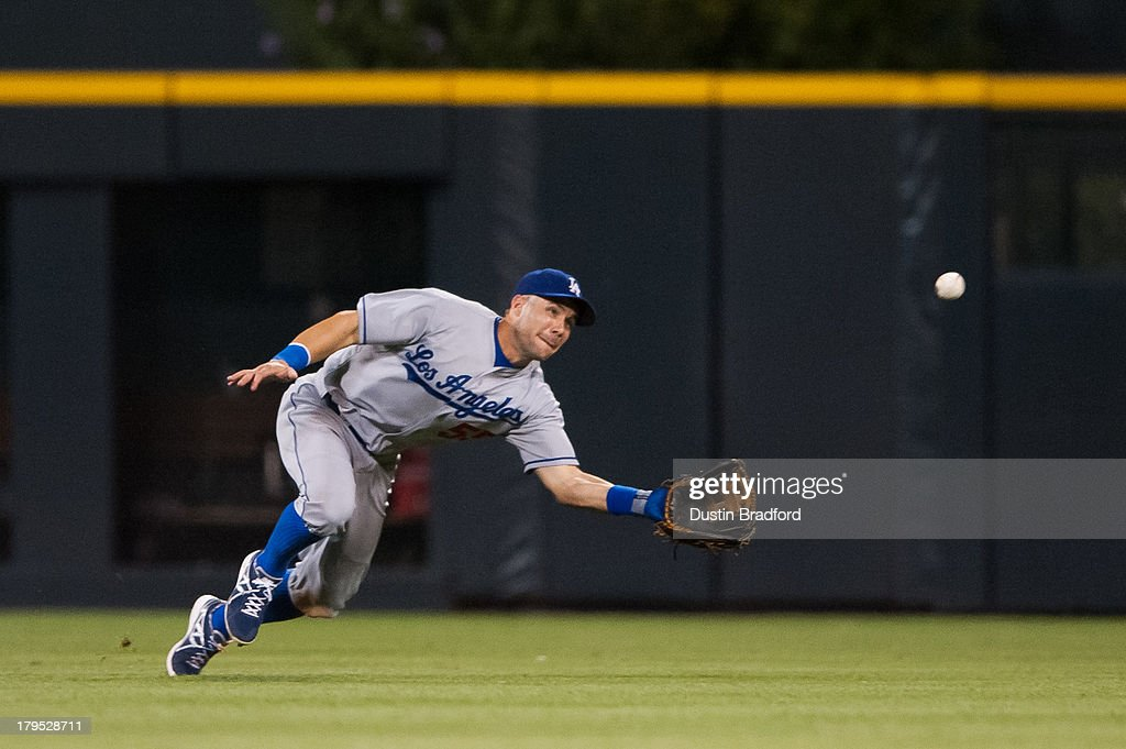 Skip Schumaker of the Los Angeles Dodgers makes a diving catch on a sacrifice fly ball hit by Troy Tulowitzki of the Colorado Rockies in the seventh...