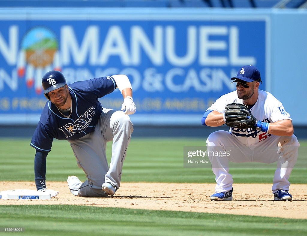 <a gi-track='captionPersonalityLinkClicked' href=/galleries/search?phrase=Skip+Schumaker&family=editorial&specificpeople=640599 ng-click='$event.stopPropagation()'>Skip Schumaker</a> #55 of the Los Angeles Dodgers reacts to a safe call at first base as <a gi-track='captionPersonalityLinkClicked' href=/galleries/search?phrase=James+Loney&family=editorial&specificpeople=636293 ng-click='$event.stopPropagation()'>James Loney</a> #21 of the Tampa Bay Rays breaks up a double play during the fourth inning at Dodger Stadium on August 10, 2013 in Los Angeles, California.