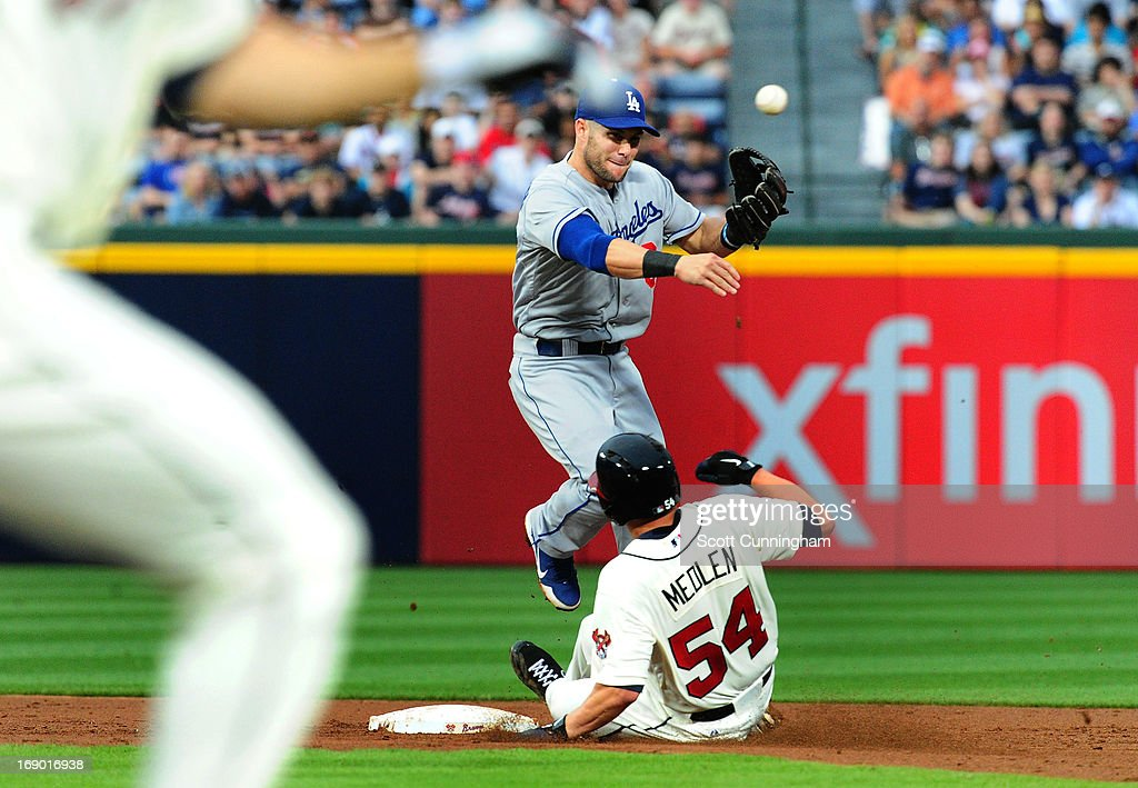 Skip Schumaker of the Los Angeles Dodgers turns a double play against Kris Medlen of the Atlanta Braves at Turner Field on May 18 2013 in Atlanta...