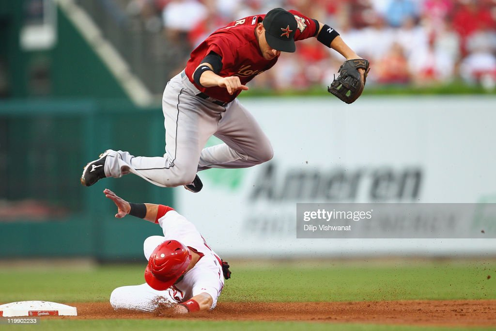 Skip Schumaker of the St Louis Cardinals breaks up a double play against Clint Barmes of the Houston Astros at Busch Stadium on July 26 2011 in St...