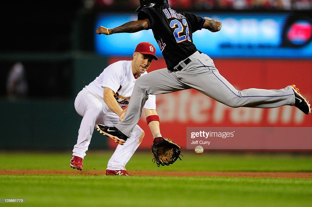Skip Schumaker of the St Louis Cardinals fields a ground ball as Willie Harris of the New York Mets leaps over the ball at Busch Stadium on September...