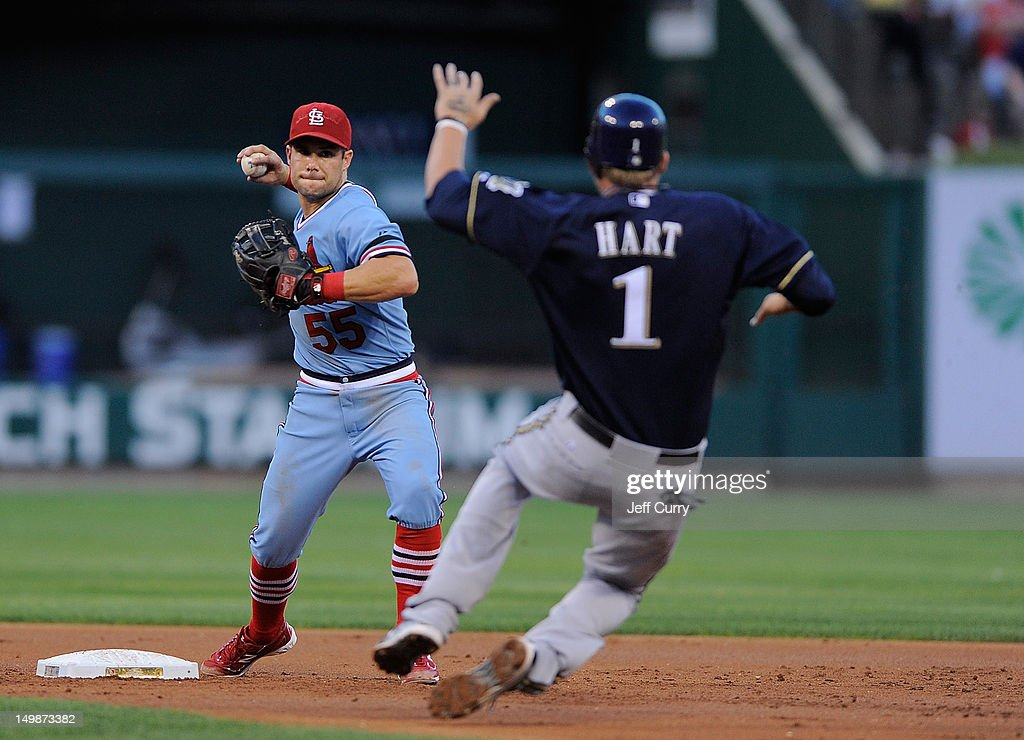 Skip Schumaker of the St Louis Cardinals turns a double play as Corey Hart of the Milwaukee Brewers slides at Busch Stadium on August 5 2012 in St...