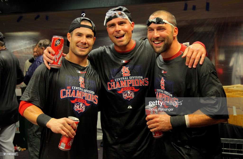 Skip Schumaker, Rick Ankiel and <a gi-track='captionPersonalityLinkClicked' href=/galleries/search?phrase=Mark+DeRosa&family=editorial&specificpeople=228401 ng-click='$event.stopPropagation()'>Mark DeRosa</a> of the St. Louis Cardinals celebrate in the clubhouse after clinching the National League Central Division by defeating the Colorado Rockies at Coors Field on September 26, 2009 in Denver, Colorado. The Cardinals defeated the Rockies 6-3.