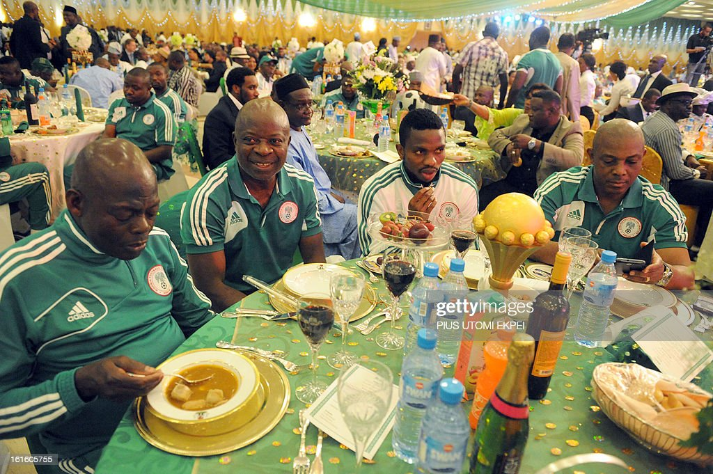 Skipper Joseph Yobo (C) keeps trophy on the dinning table flanked by Assistant Coach Sylvanus Okpala (2 L) and Coach Stephen Keshi during the presidential banquet in honour of the victorious team in Abuja February 12, 2013. The newly crowned African champions Nigerian Super Eagles arrives in Abuja to a warm reception by fans and government officials after defeating Burkina Faso to win the 2013 African Cup of Nations in South Africa. AFP PHOTO/PIUS UTOMI EKPEI