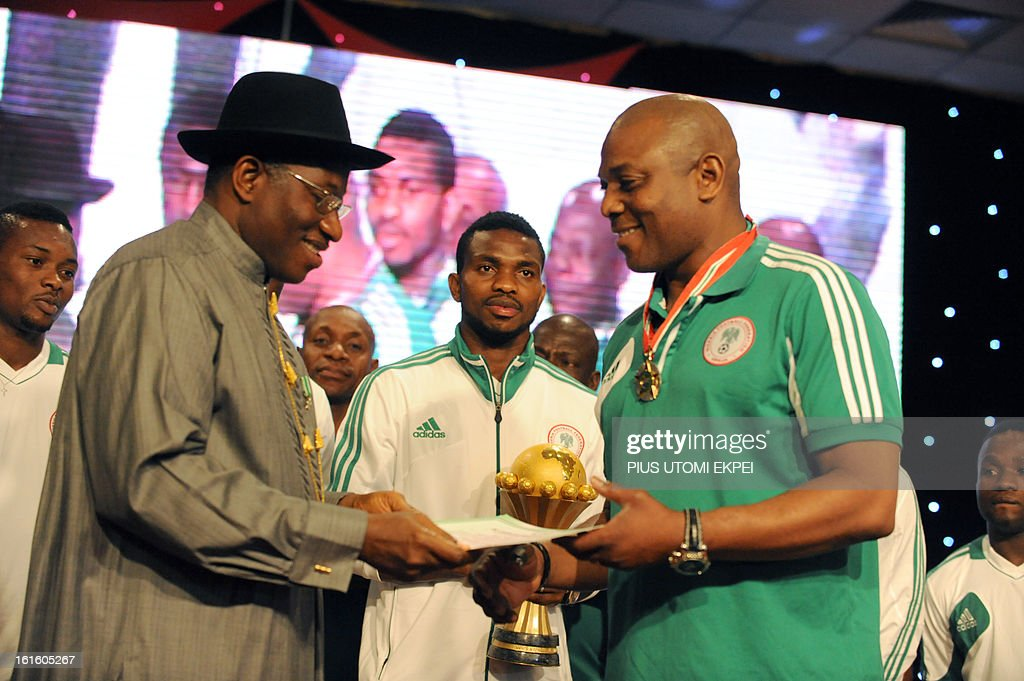 Skipper Joseph Yobo (C) looks on while holeding the winning trophy, as the Nigerian President Goodluck Jonathan presenting awards to national football Coach Stephen Keshi (R) during the presidential banquet in honour of the victorious team in Abuja February 12, 2013. The newly crowned African champions Nigerian Super Eagles arrives in Abuja to a warm reception by fans and government officials after defeating Burkina Faso to win the 2013 African Cup of Nations in South Africa.